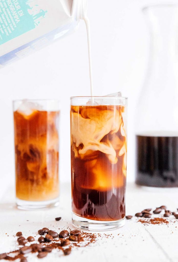 Pouring cream into a tall glass of cold brew coffee