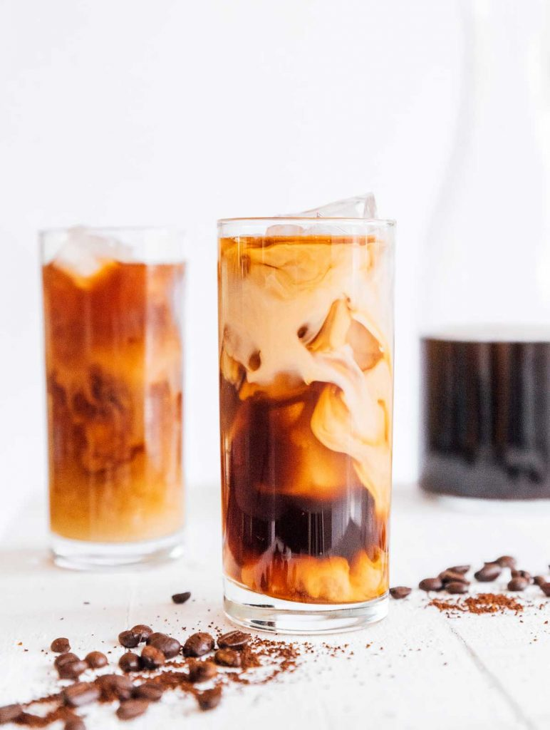 Two tall glasses of iced cold brew coffee with cream