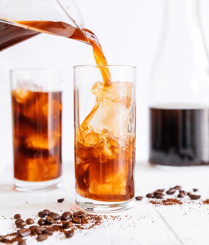 Pouring cold brew coffee into a tall glass of ice