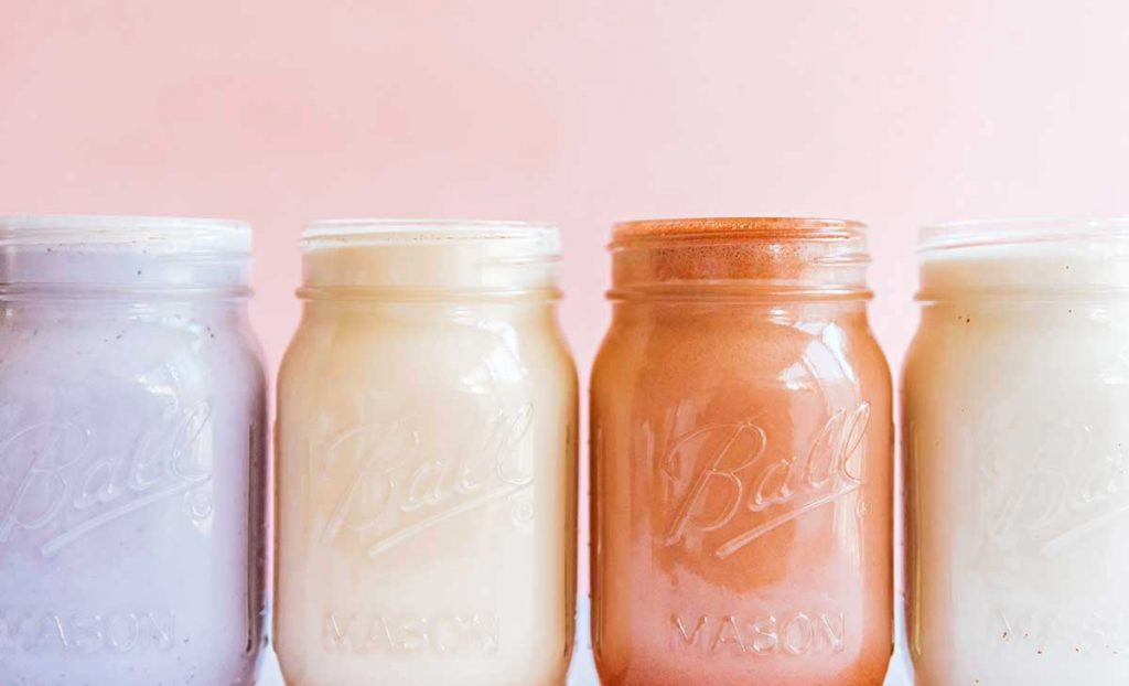 For mason jars in a row filled with different almond milk: berry, vanilla, chocolate, and sweetened