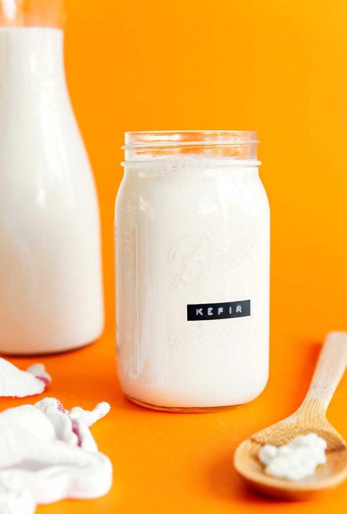 Kefir in a mason jar on an orange background