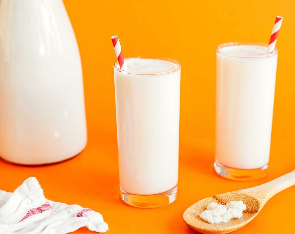 Kefir in a glass with a striped straw on an orange background