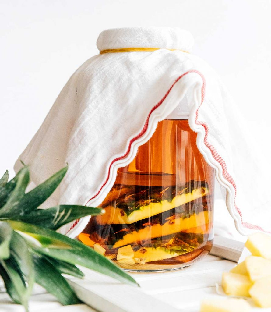Making tepache in a glass jug on a white background