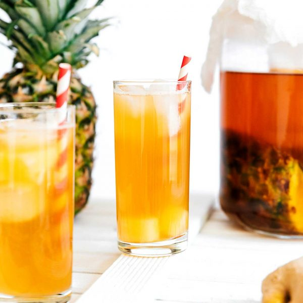 Tepache in a glass with a red striped straw and pineapple