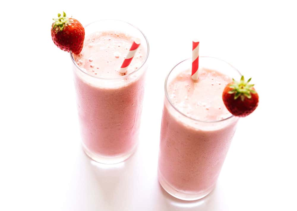 Two tall glasses filled with strawberry cottage cheese smoothies and topped with a strawberry