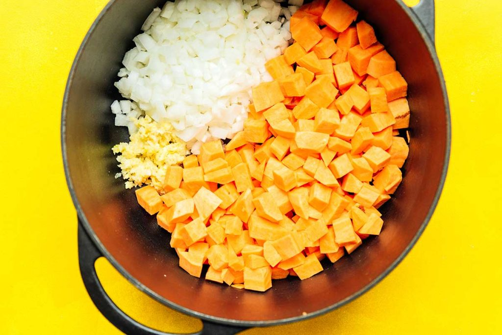 A sauce pot filled with diced sweet potato, chopped white onion, and minced garlic