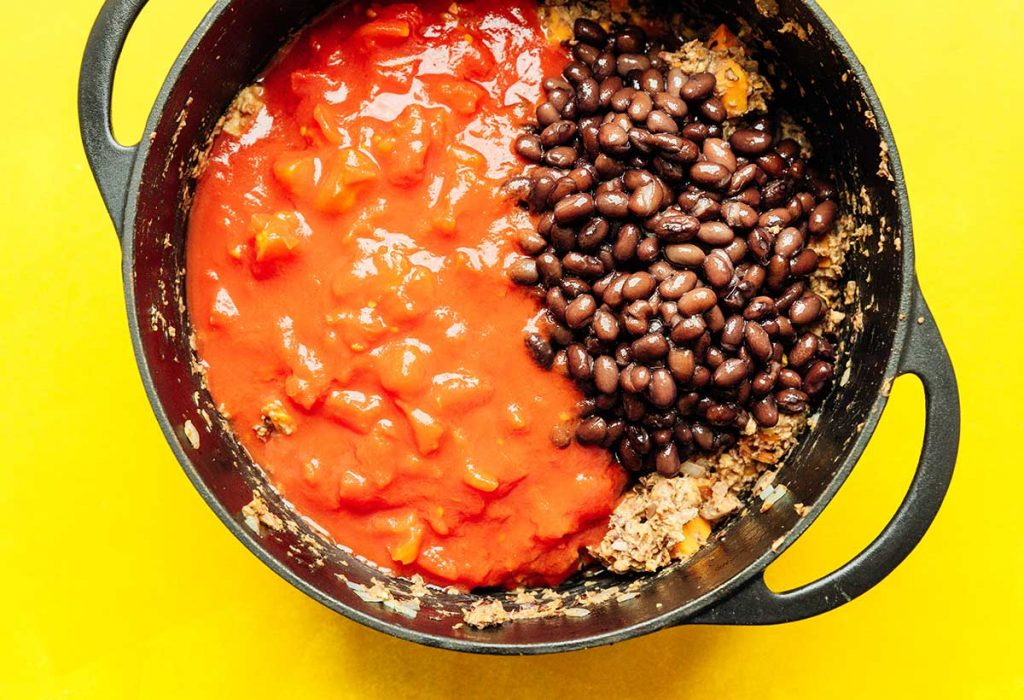 A sauce pot filled with diced sweet potato, chopped white onion, minced garlic, black bean chili meat, diced tomatoes, and black beans