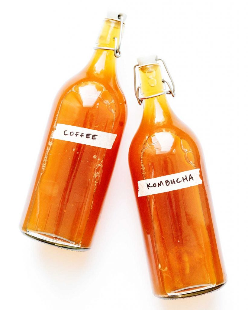 Coffee kombucha in fermentation bottles on a white background