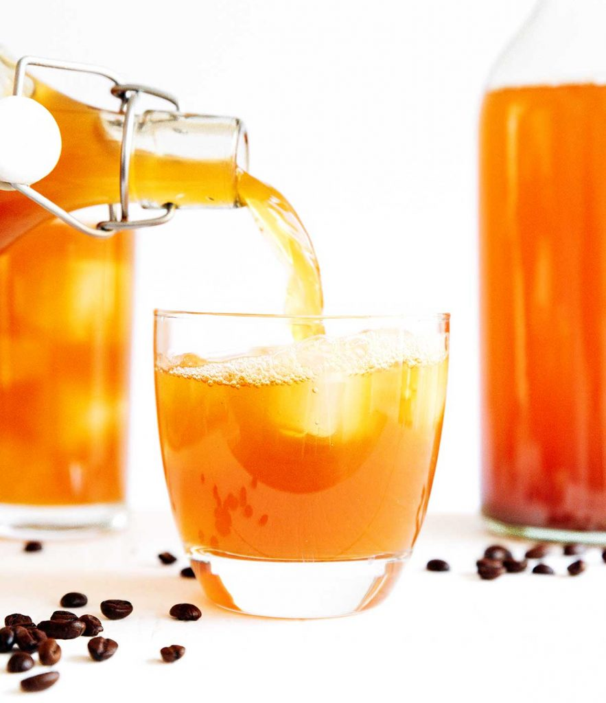 Pouring coffee kombucha in a glass with ice