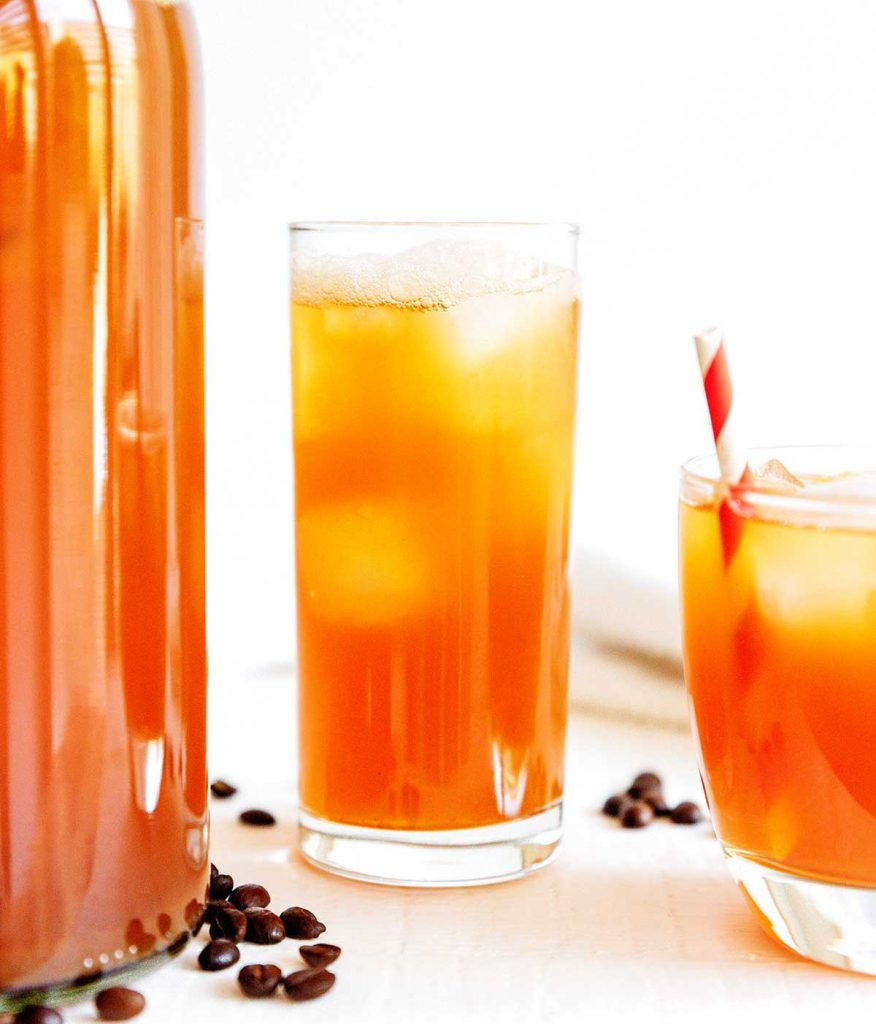 Coffee kombucha in a glass with ice and a straw