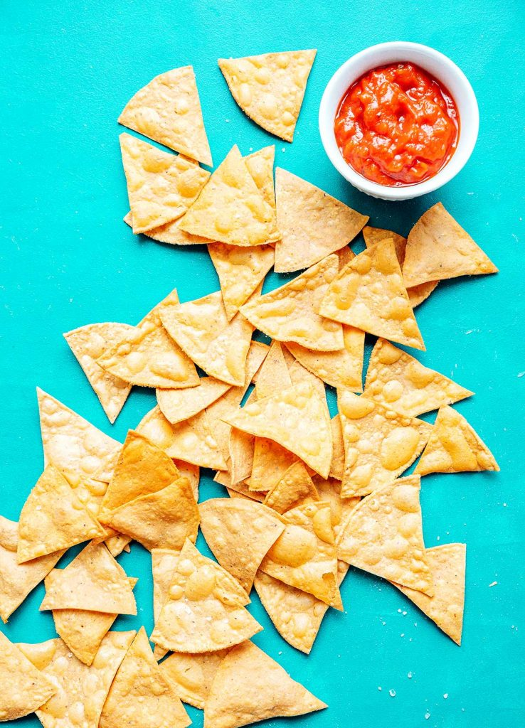 Tortilla chips on a blue background with salsa