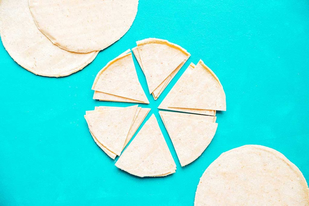 Cutting corn tortillas into triangles