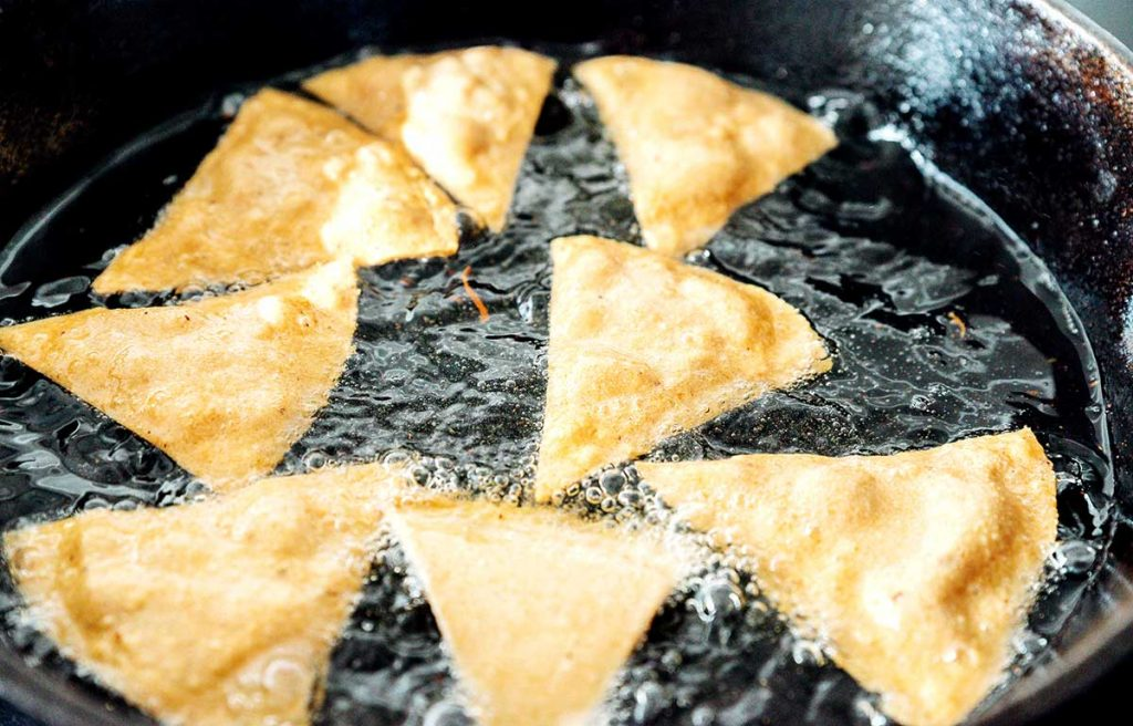 Frying corn tortilla chips in a cast iron skilelt