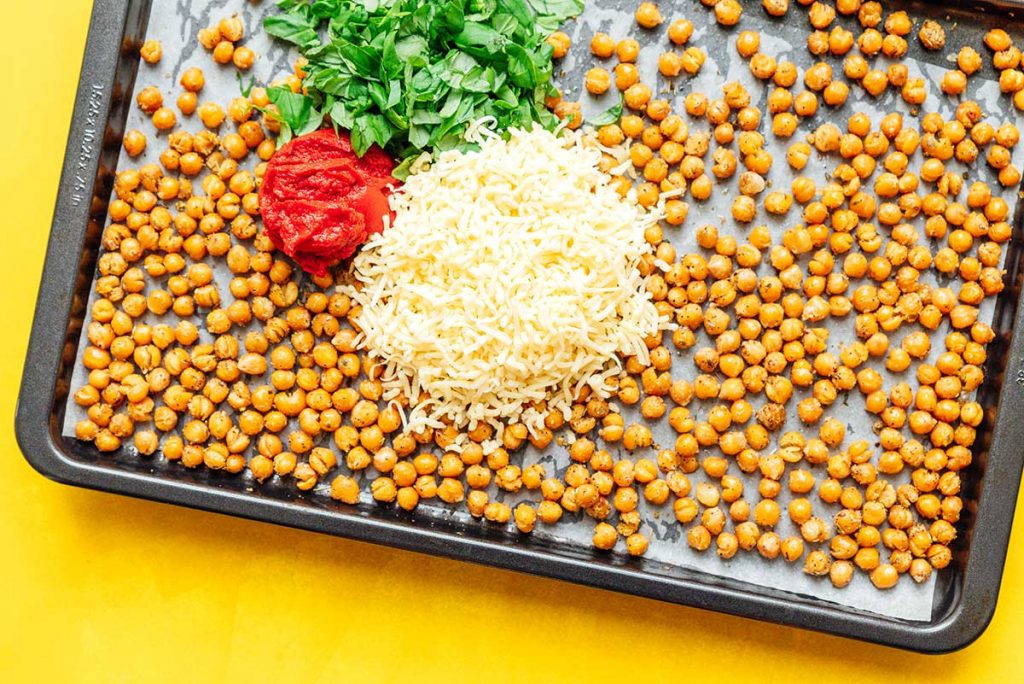 A sheet pan filled with a single layer of roasted chickpeas topped with basil, tomato paste, and mozzarella
