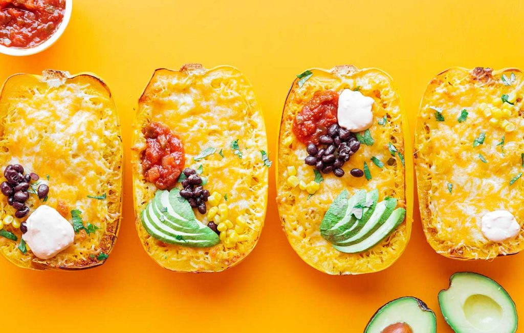 Four spaghetti squash halves lined up and filled with burrito bowl ingredients