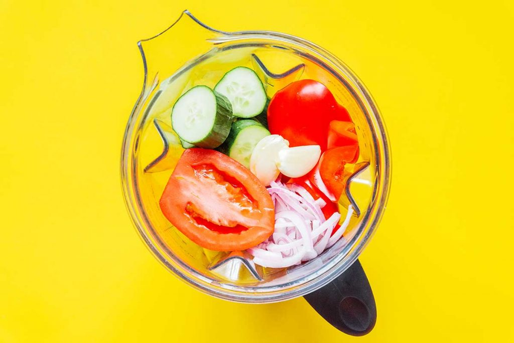 A blender filled with sliced cucumber, chopped onion, sliced roma tomatoes, and garlic cloves
