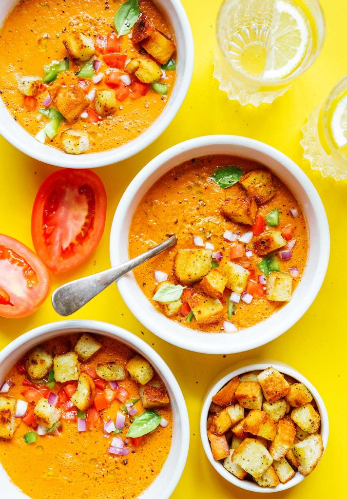 Two bowls of tomato gazpacho topped with croutons, tomatoes, green peppers, and red onion