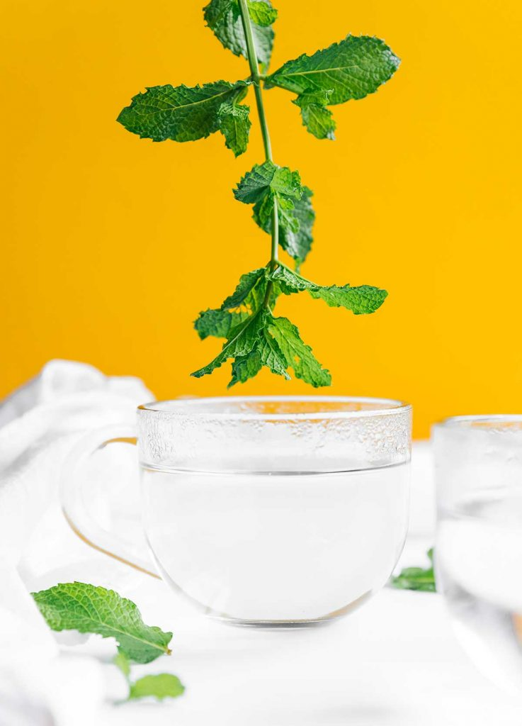 Adding fresh mint to a glass of hot water