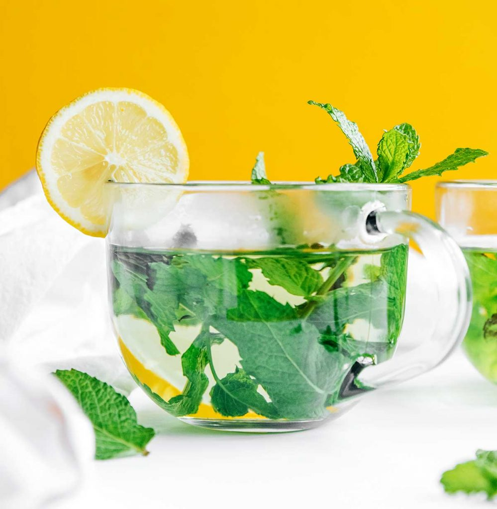Fresh mint tea in a clear glass with a lemon