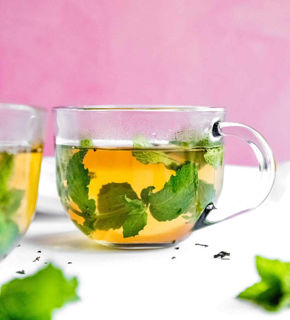 Fresh mint tea to a glass on a pink background