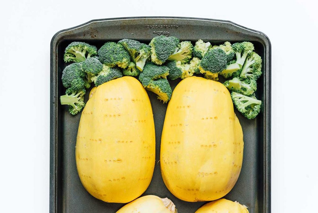 Two cups of broccoli and two spaghetti squash halves placed face-down on a baking sheet