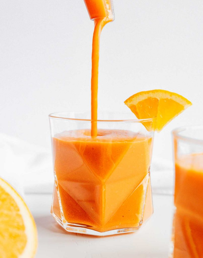 Pouring carrot smoothie with citrus and ginger from a blender into a glass