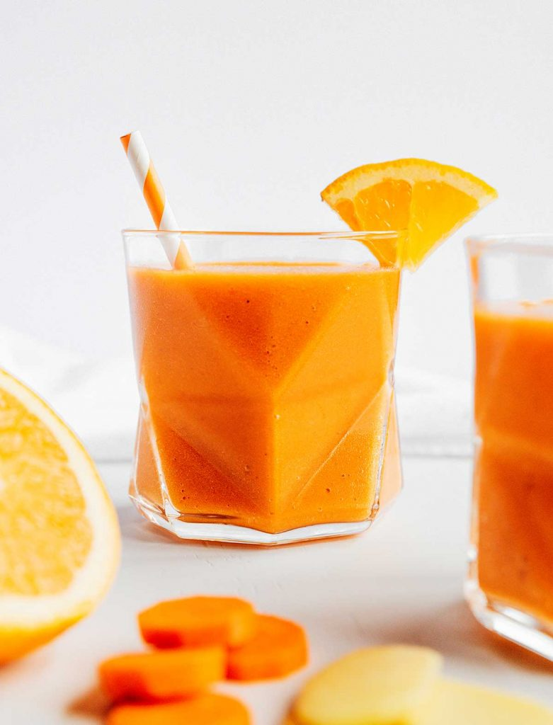 A glass filled with freshly blended carrot smoothie with citrus and ginger and decorated with an orange slice
