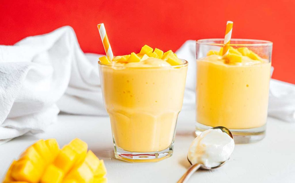 Two glasses of mango smoothie, a spoon filled with Greek yogurt, and a diced mango