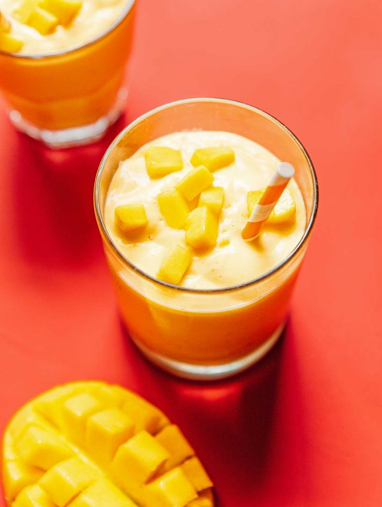 A glass filled with mango smoothie and topped with diced mangos
