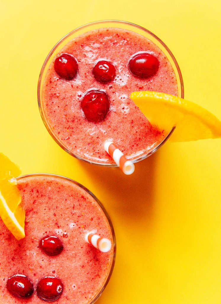 An image looking down on the tops of two glasses filled with cranberry smoothie, topped with cranberries and decorated with orange slices
