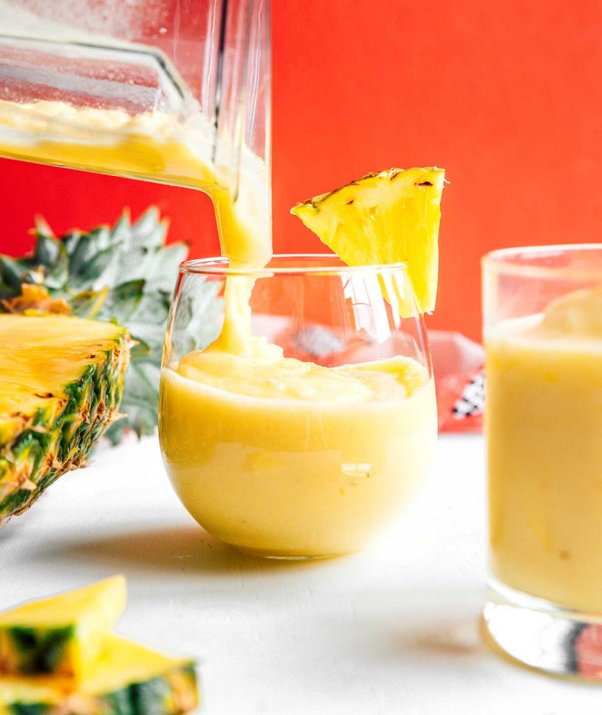 Pouring pineapple smoothie into a glass