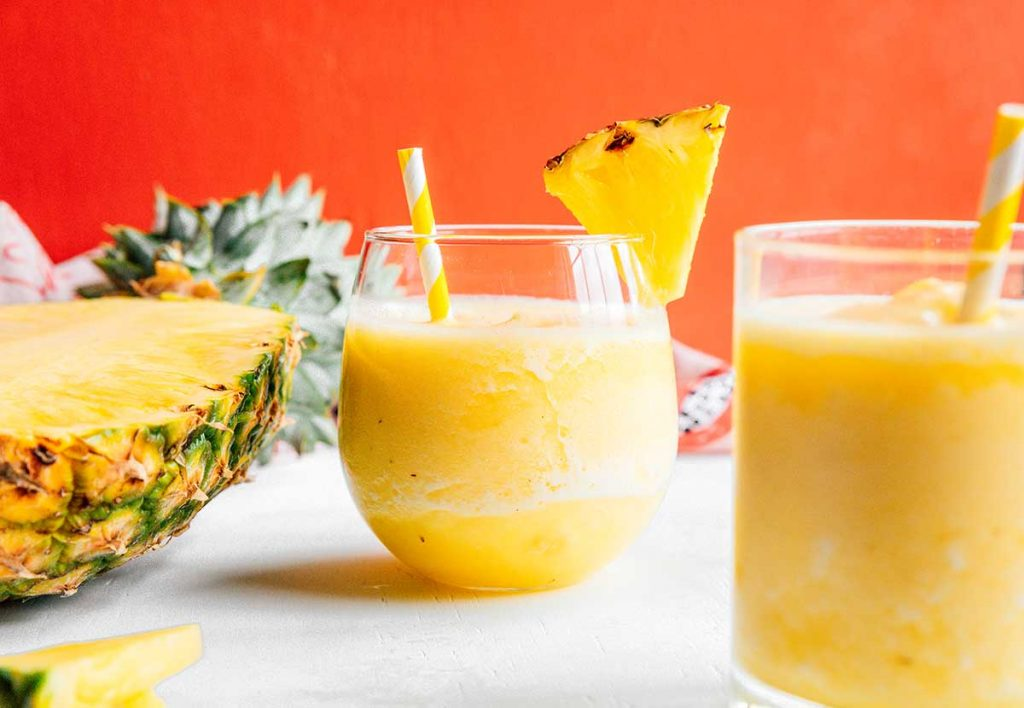 Two glasses filled with pineapple smoothie and half of a pineapple laying skin-down on a white background