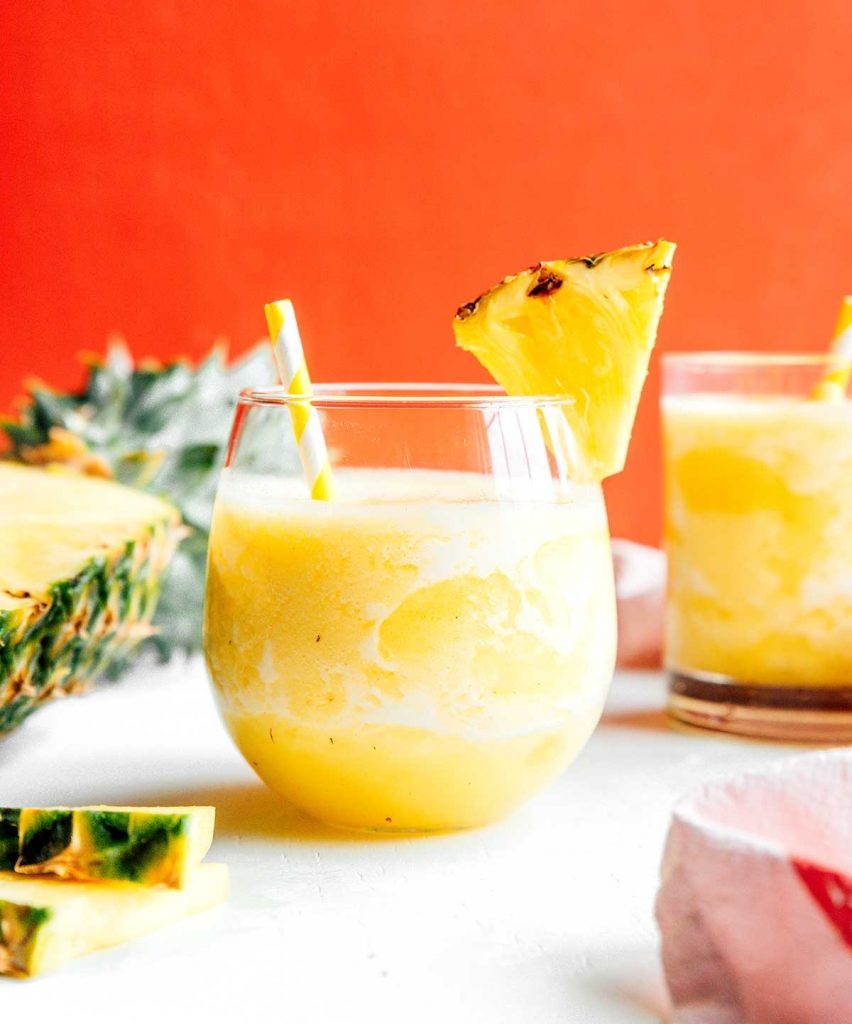 A glass filled with pineapple smoothie and decorated with a slice of pineapple