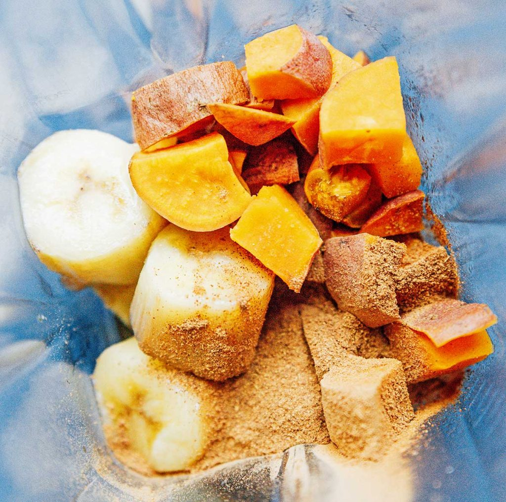 A blender filled with frozen banana chunks, diced sweet potato, and spices