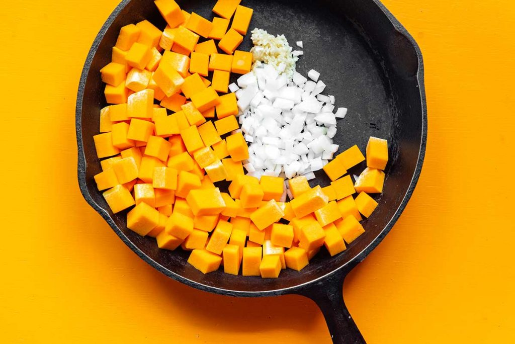 A cast iron skillet filled with diced butternut squash, chopped onion, and minced garlic