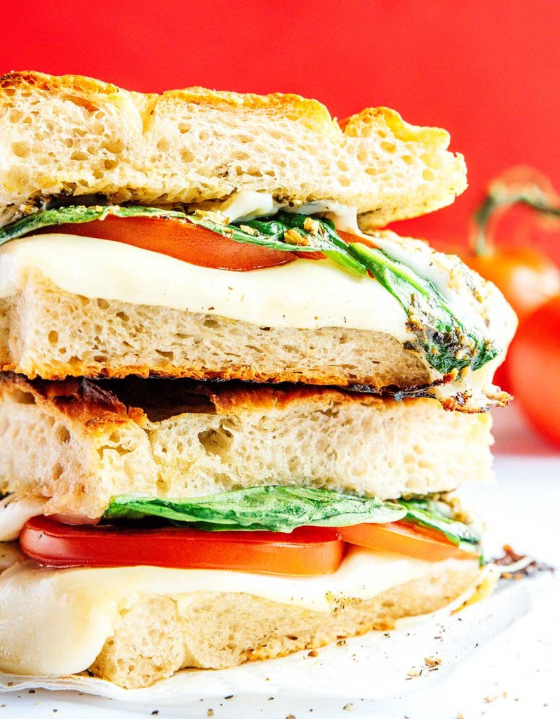 Close up view of two caprese paninis stacked on top of the other and filled with spinach, tomato, mozzarella, and pesto