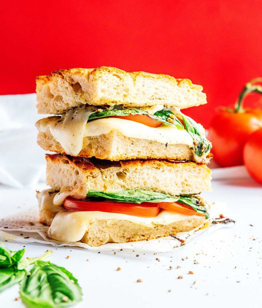 Two caprese paninis stacked on top of the other and filled with spinach, tomato, mozzarella, and pesto