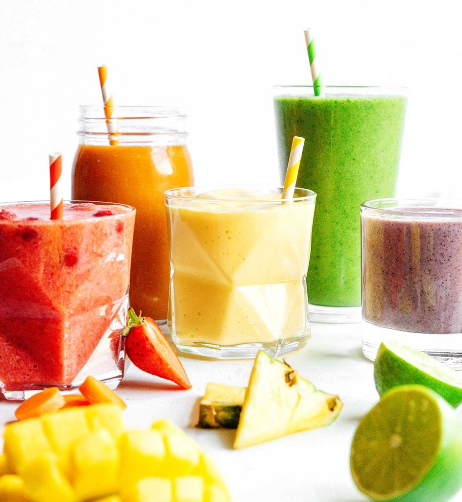 Different smoothies arranged in rainbow on white background