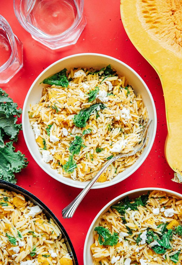 A white bowl filled with butternut squash orzo salad