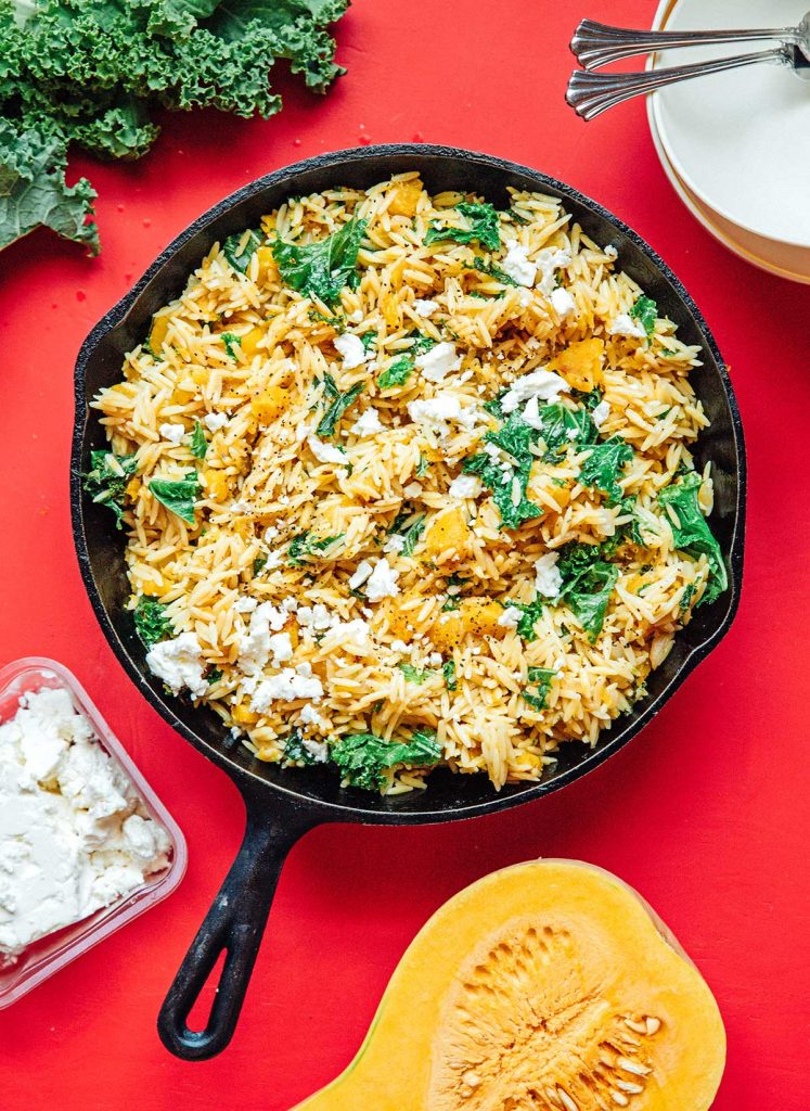 A cast iron skillet filled with cooked kale and white onion, butternut squash, orzo, and various spices