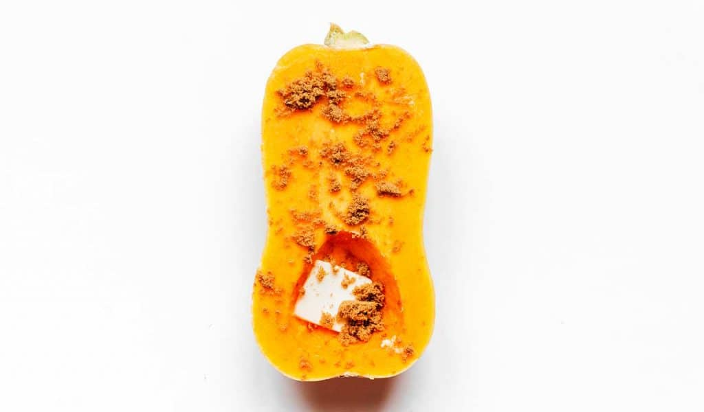 Half of a butternut squash coated with butter, brown sugar, and cayenne pepper