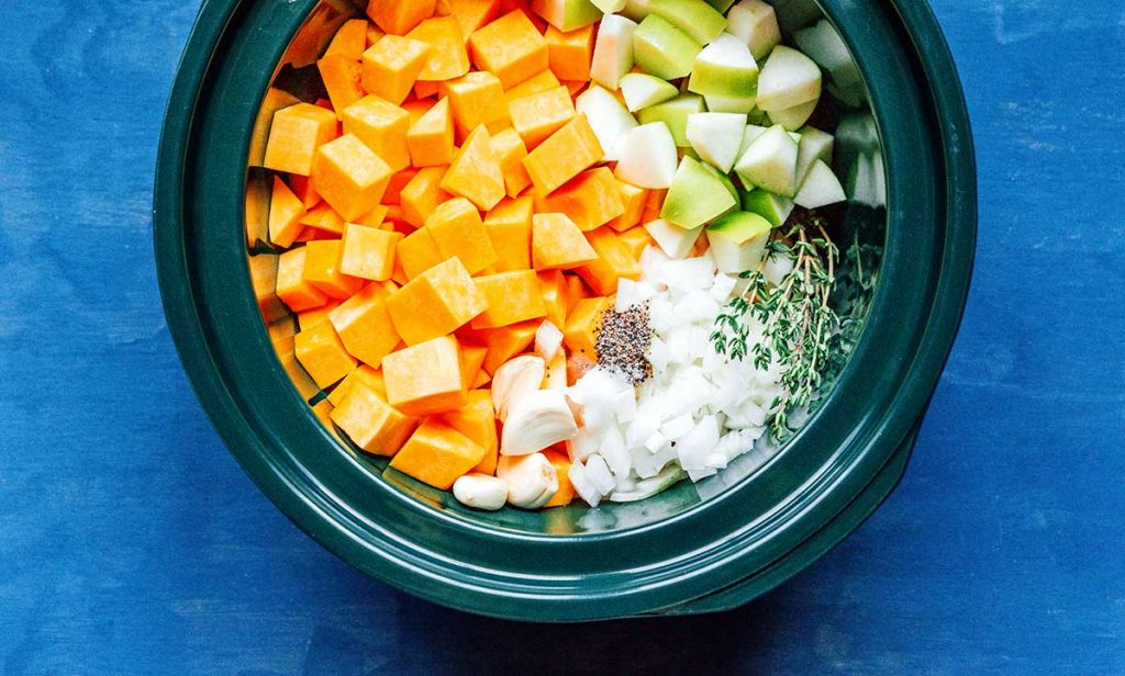 A slow cooker filled with diced butternut squash, diced green apple, diced white onion, thyme, and various seasonings