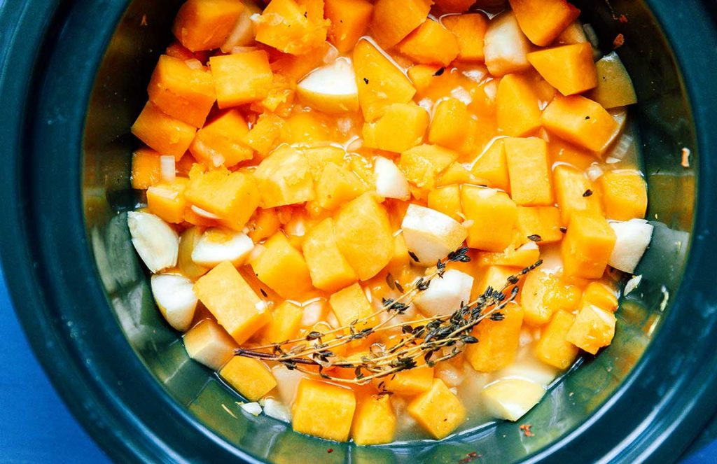 A bunch of fresh thyme laid on top of butternut squash, green apple, and white onion cooking in a slow cooker