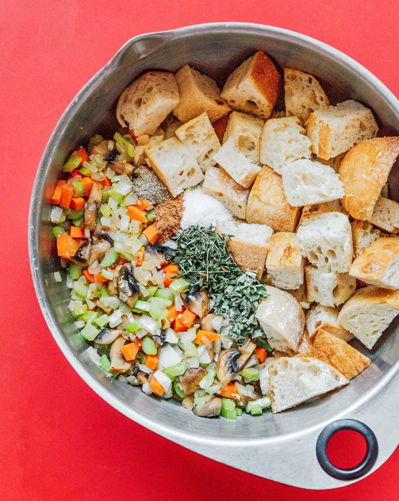 A mixing bowl filled with vegetable bread stuffing ingredients and seasonings