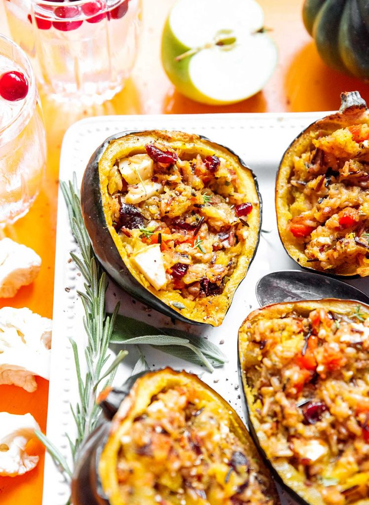 A close up view of four stuffed acorn squash halves on a white serving plate