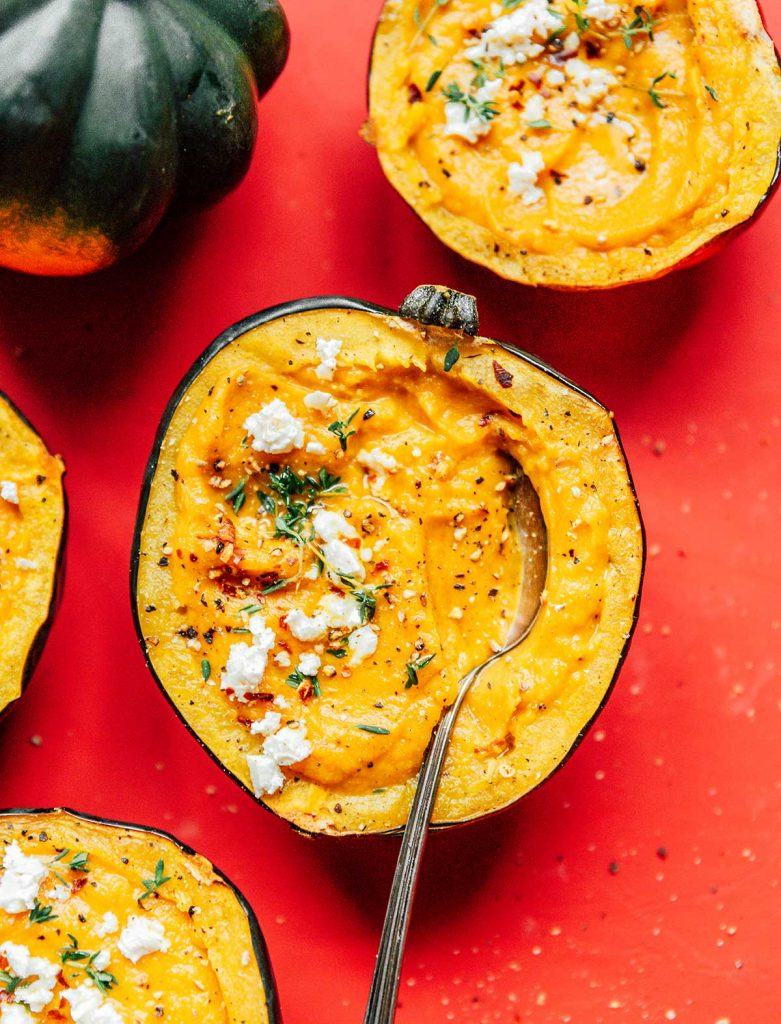 A spoon dipped into an acorn squash half filled with acorn squash soup