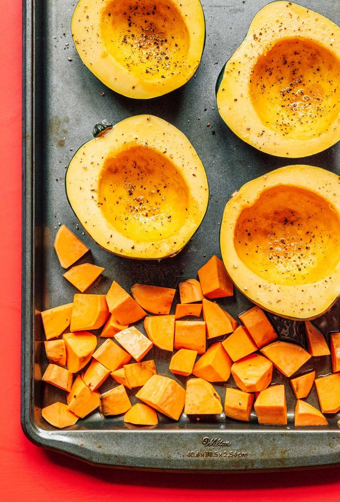 Four acorn squash halves and cubed sweet potatoes laid out on a baking sheet and topped with olive oil, salt, and pepper