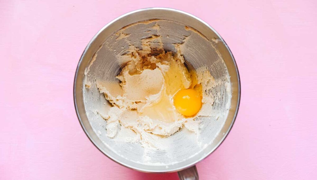 A metal mixing bowl filled with a butter and sugar mixture with an unmixed egg and vanilla on top