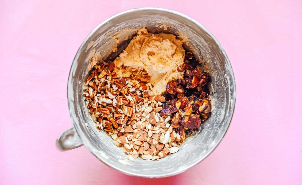 A metal mixing bowl filled with chewy date cookie ingredients