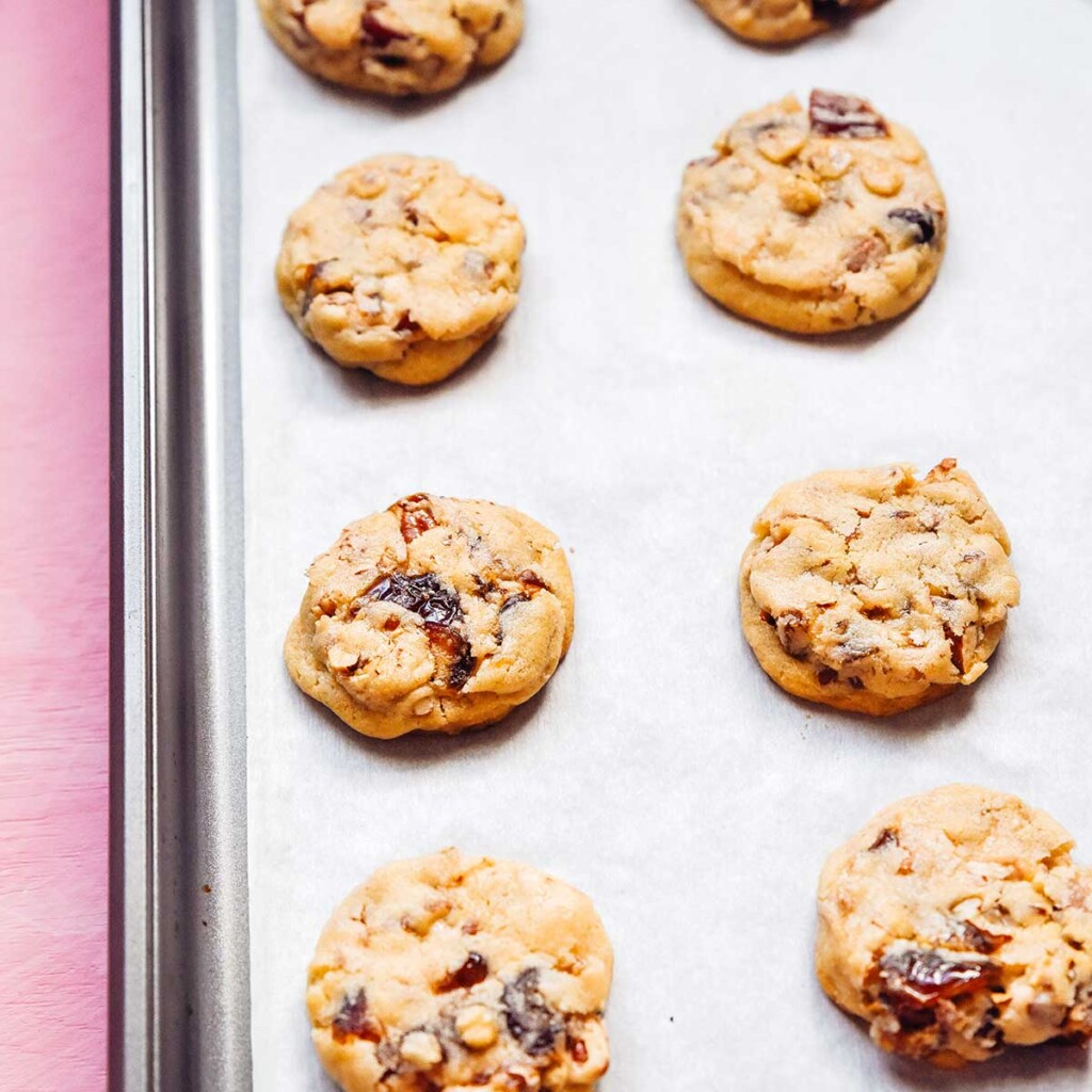 Flattened chewy date cookies cooling on a parchment-lined baking sheet